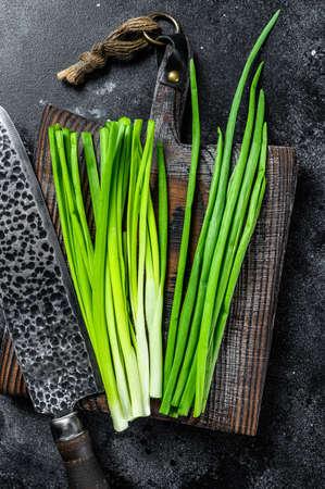 Fresh green onions on a cutting board. Black background. Top view 免版税图像