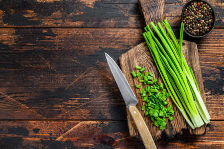 Cut Green onions chives on a cutting board. Dark wooden background. Top view. Copy space