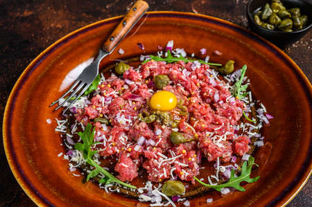 French cuisine Beef tartare with raw egg yolk. Dark background. Top view