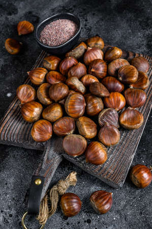 Raw chestnuts on a wooden cutting board. Black background. Top view