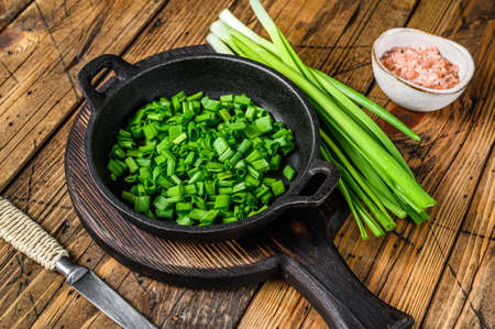 Sliced Green onions in a pan. wooden background. Top view
