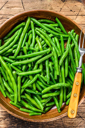 Cooked green beans in a wooden plate. wooden background. top view