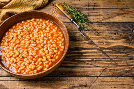 White beans in tomato sauce in a wooden plate. wooden background. top view. Copy space 免版税图像