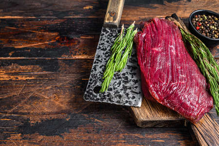 Venison raw meat steak on a cuuting board with rosemary. Black background. Top view. Copy space