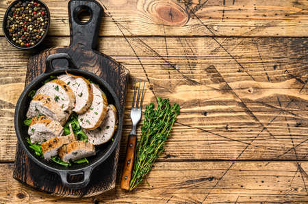 Sliced grilled pork tenderloin steak in a pan. Wooden background. Top view. Copy space