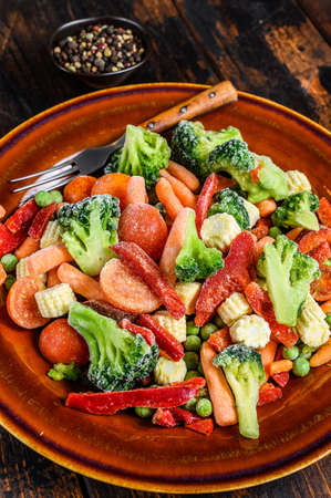 Frozen cut Vegetables, broccoli, sweet peppers, tomatoes, carrots, peas and corn on a plate. Dark Wooden background. top view