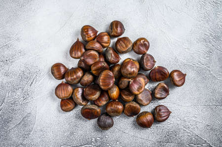 Raw chestnuts on a wooden table. White background. Top view