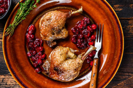 Roasted Christmas duck legs with cranberrie sauce. Dark wooden background. top view