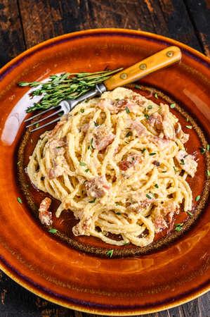 Italian Spaghetti Carbonara pasta with bacon, hard parmesan cheese and cream sauce. Dark Wooden background. top view 免版税图像