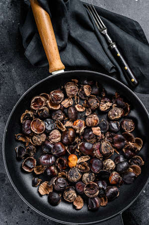 Roast grilled chestnuts on a wooden table. Black background. Top view