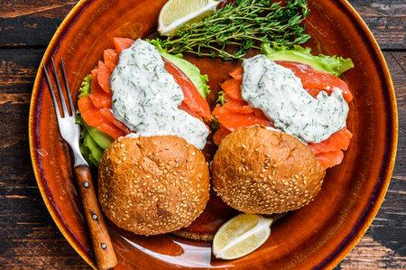Fishburger with salted fish salmon, avocado, burger bun, mustard sauce and Iceberg salad. Dark wooden background. top view