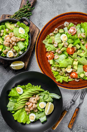 Set of salads with avocado, prawns, shrimps and greens in bowls. White background. top view 免版税图像
