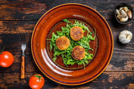 Roasted chickpeas falafel patties with arugula on a plate. Dark wooden background. Top view 免版税图像