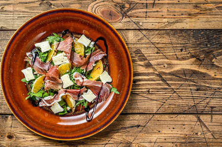Salad with prosciutto parma ham, parmesan cheese, arugula and tangerine on a plate. Wooden background. Top view. Copy space 免版税图像