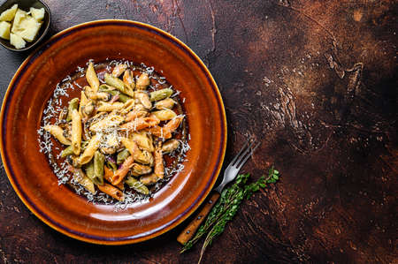 Seafood color Penne pasta in cream sauce on a plate. Dark background. Top view. Copy space 免版税图像