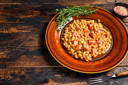 Kidney beans with smoked sausage and tomato sauce in a plate. Dark wooden background. Top view. Copy space