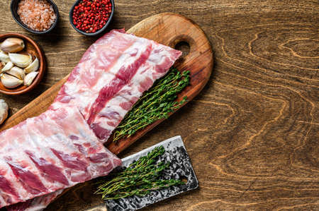 Fresh Raw lamb rack spare ribs with spices on a cutting board. Wooden background. Top view. Copy space