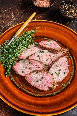Sliced Roast beef sirloin tender steak on a rustic plate. Dark background. Top view 免版税图像