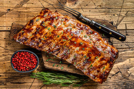 Grilled and smoked pork spare ribs. Wooden background. Top view