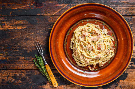 Italian Spaghetti Carbonara pasta with bacon, hard parmesan cheese and cream sauce. Dark Wooden background. top view. Copy space