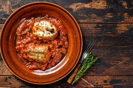 Roast hake white fish fillet with tomato sauce in a plate. Dark background. Top view. Copy space 免版税图像