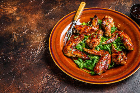 Bbq buffalo chicken wings on a plate with arugula. Dark background. Top view. Copy space