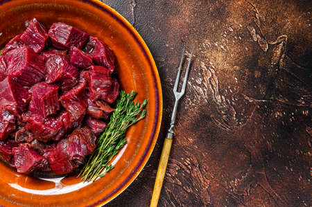 Raw diced elk meat steak for a goulash on a plate. Dark background. Top view. Copy space
