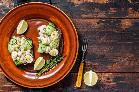 Scandinavian Sandwiches with shrimp, prawns, quail eggs and cucumber on rye bread. Dark Wooden background. top view. Copy space 免版税图像