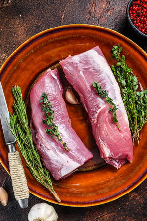Fresh pork tenderloin meat with rosemary and thyme. Dark background. Top view