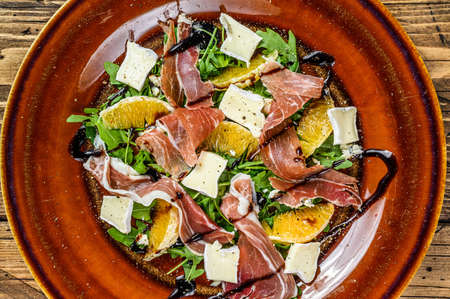 Salad with prosciutto parma ham, parmesan cheese, arugula and tangerine on a plate. Wooden background. Top view 免版税图像