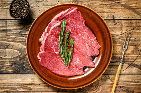 Raw beef meat chop rump steak on a plate. wooden background. Top view 免版税图像