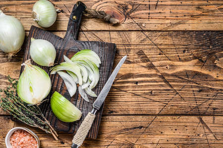 Sliced Raw white onion on a wooden cutting board. Wooden background. Top view. Copy space 免版税图像