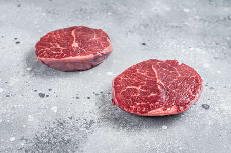 Raw fillet Mignon beef steaks on a butcher board. Gray background. Top view