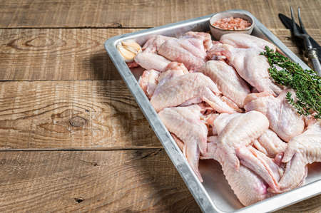 Fresh Raw chicken wings Poultry meat in a kitchen tray with herbs. Wooden background. Top view. Copy space Фото со стока