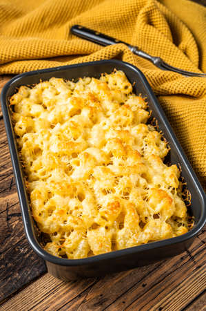 Baked Mac and cheese American dish with Cheddar sauce. Wooden background. Top view Фото со стока