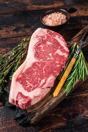 Raw new york strip beef steak or striploin on a wooden board. Dark wooden background. Top view