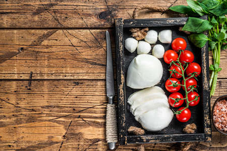 Mozzarella cheese, basil and tomato cherry in wooden tray, Caprese salad. wooden background. Top view. Copy space