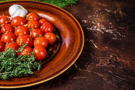 Marinated Preserve cherry tomatoes in a rustic plate with garlic and thyme. Dark background. Top view. Copy space