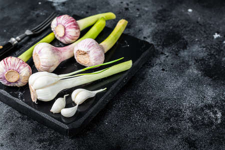Raw Spring young garlic bulbs and cloves on marble board. Black background. Top view. Copy space