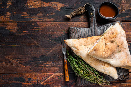 Homemade Calzone closed pizza with ham and cheese on wooden board. Dark wooden background. Top view. Copy space Фото со стока