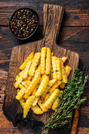 Baked Crinkle French fries potatoes sticks or chips on a wooden board. Dark wooden background. Top view
