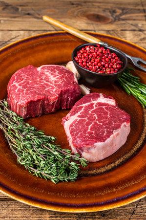 Raw Fillet Mignon tenderloin meat beef steaks on rustic plate. wooden background. Top view Фото со стока