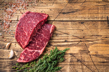Raw denver or top blade meat steak on a butchery table with herbs. wooden background. Top view. Copy space Фото со стока