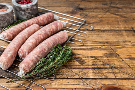 Raw sausages - Bratwurst with pork meat on a griil. Wooden background. Top view. Copy space