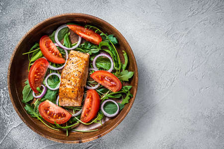 Salmon fillet steak salad with green leaves arugula, avocado and tomato in a wooden plate. White background. Top view. Copy space