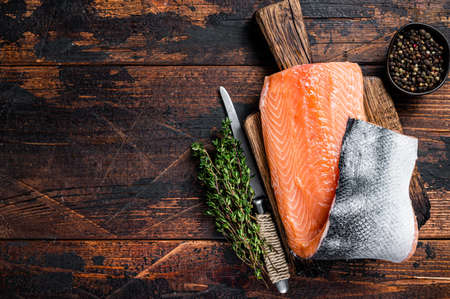 Salmon fillet fish on a wooden board with herbs and salt. Dark wooden background. Top view. Copy space Фото со стока