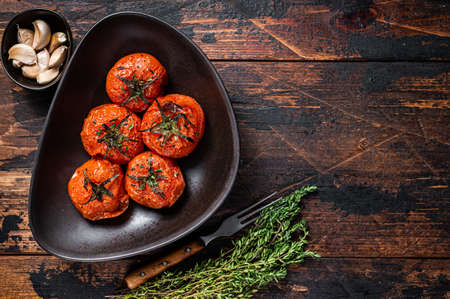 Oven Roasted cherry tomatoes with thyme and garlic in a plate. Dark wooden background. Top view. Copy space