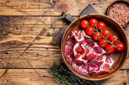 Italian sliced cured coppa ham with spices. wooden background. Top view. Copy space