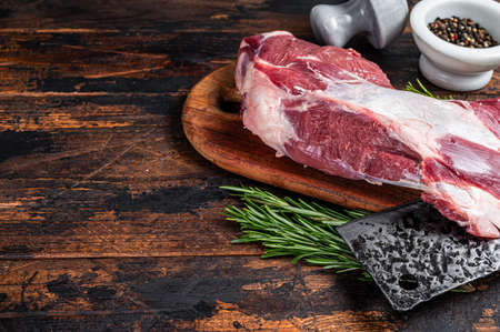 Raw lamb or goat shoulder meat on the bone on a wooden butcher cutting board with cleaver. Dark wooden background. Top view. Copy space
