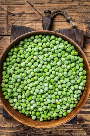 Cold Frozen green peas in a wooden plate. Wooden background. Top view